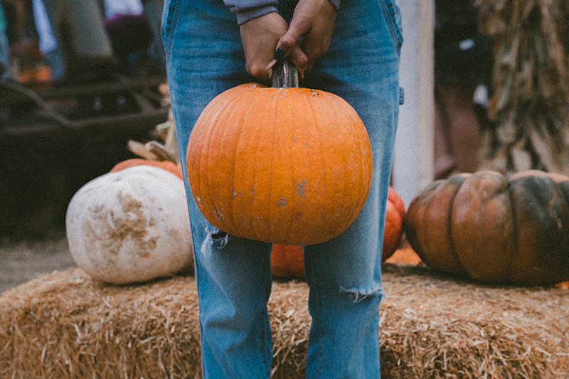 woman carrying a pumpkin with a haystack behind her