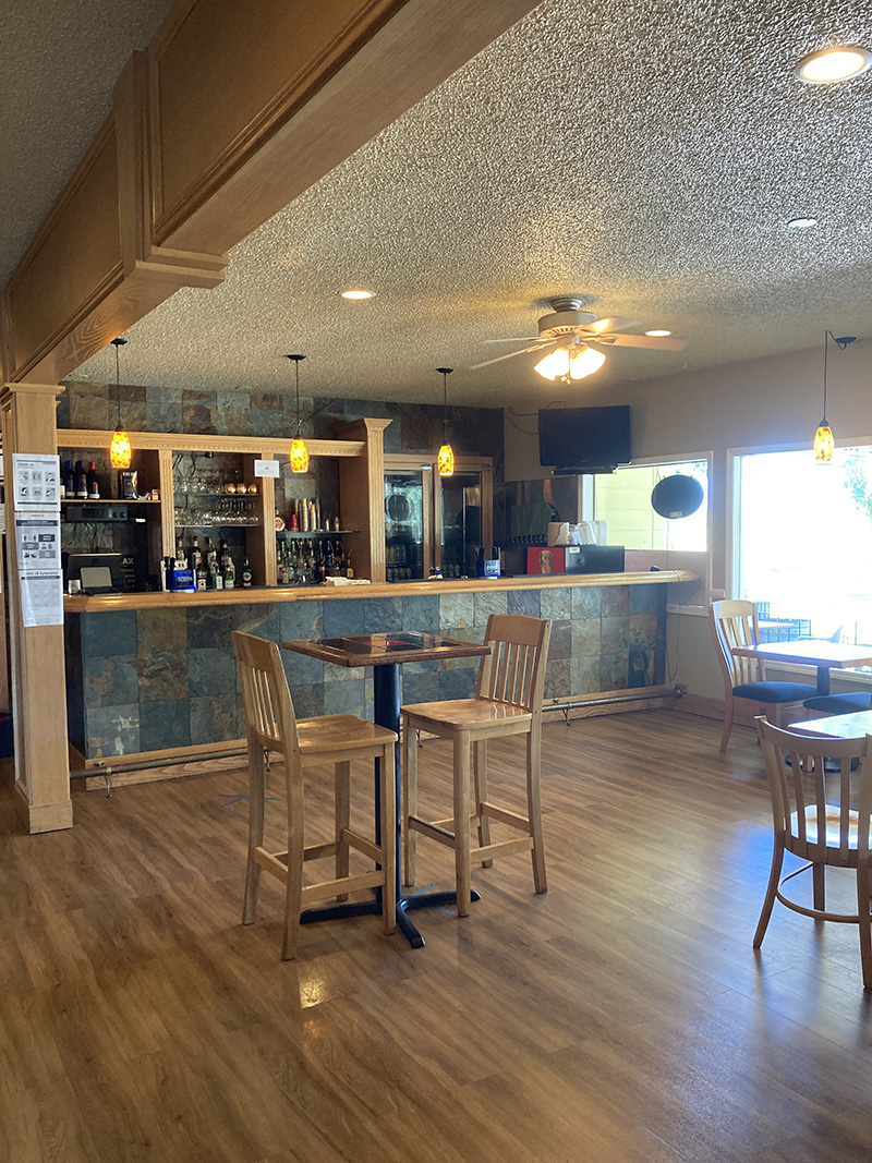 restaurant and bar with slate stone pavers as the counter wall and wood floors, tables, and chairs