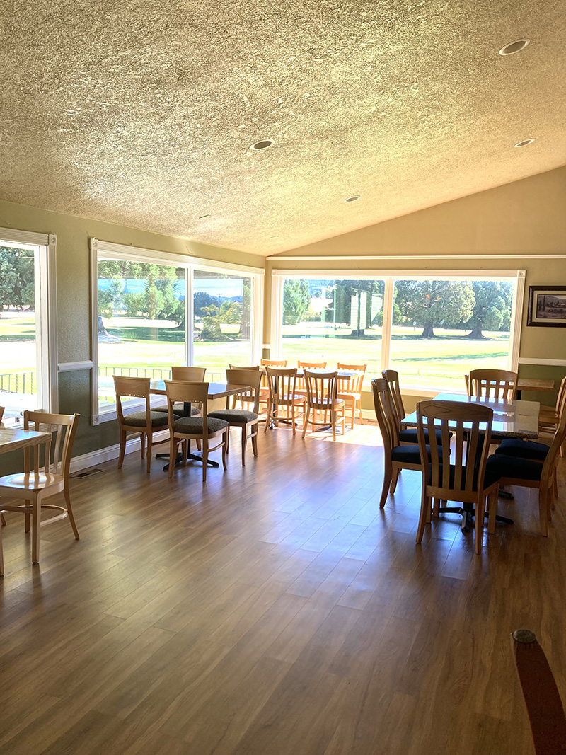 restaurant with wood floors, tables, and chairs as well as tall windows to the golf course
